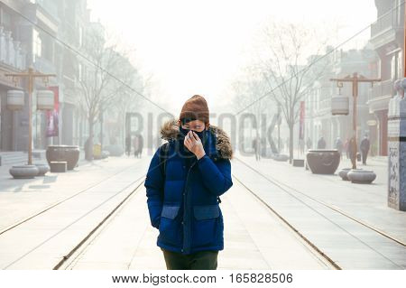 Asian Man Walking And Wearing A Face Mask In A Foggy Smog And Hazy Day As He Suffers From Severe Air