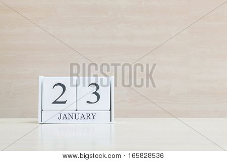 Closeup surface white wooden calendar with black 23 january word on blurred brown wood desk and wood wall textured background with copy space selective focus at the calendar