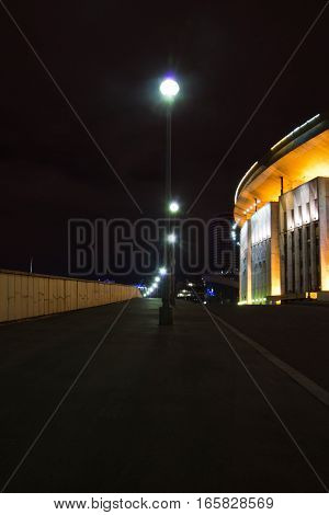 stadium and street lamps in the city at night