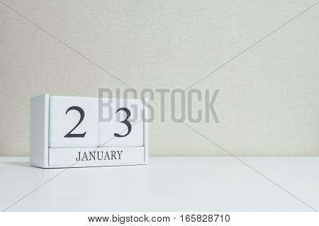 Closeup white wooden calendar with black 23 january word on blurred white wood desk and cream color wallpaper in room textured background with copy space selective focus at the calendar