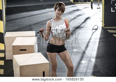 Athletic smiling girl with a skipping rope stands in the gym and looks into the camera. She wears a black shorts, red top and gray sleeveless. Daylight shines on her from behind. Horizontal.