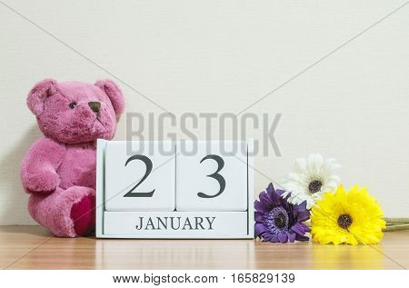 Closeup surface white wooden calendar with black 23 january word on brown wood desk and cream color wallpaper in room textured background with copy space selective focus at the calendar