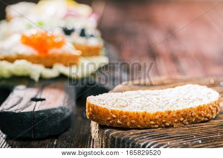 Bran toast on wooden board. Sandwiches with farmer cheese and various tops on the background