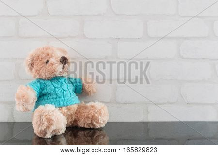 Closeup cute brown bear doll on black glass table and white brick wall textured background with copy space