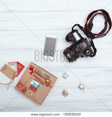 top view of Christmas gift boxes,  smart phone and camera on  white wooden background. mood board