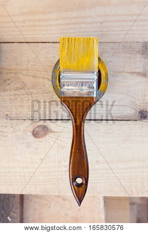 Bank with yellow paint and a brush top view. Brush with wooden handle closeup