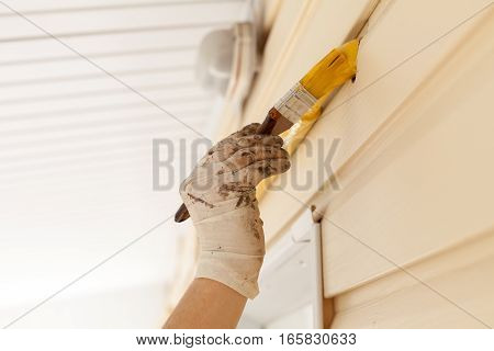 Worker with gloves colors the metal gas pipe of yellow paint with a brush with a wooden handle.