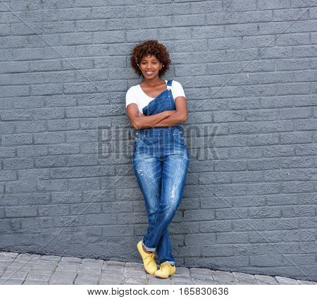 Smiling African Woman Standing Against Gray Wall