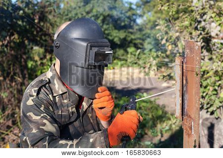 Man in welding mask welds metal corner. Welding metal. Steel welder. Welder working with electrode.
