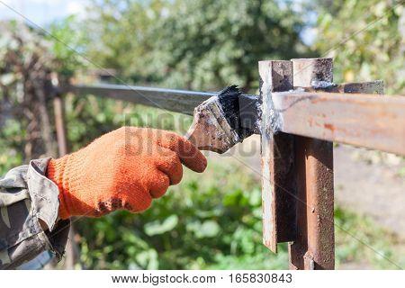 The man paints a black paint metal profile construction.
