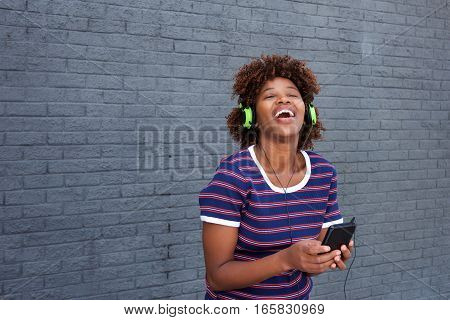 African Woman Enjoying Music With Headphones And Mobile Phone