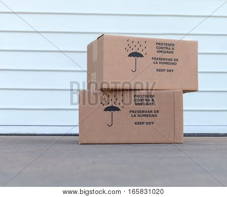 Pile of cardboard boxes over white warehouse door background stock photo