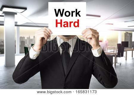businessman in modern office hiding face behind sign work hard