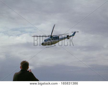 Picture of a man photographing a flying helicopter