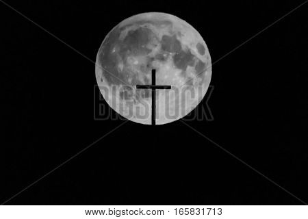 The moon with a church cross in front of it
