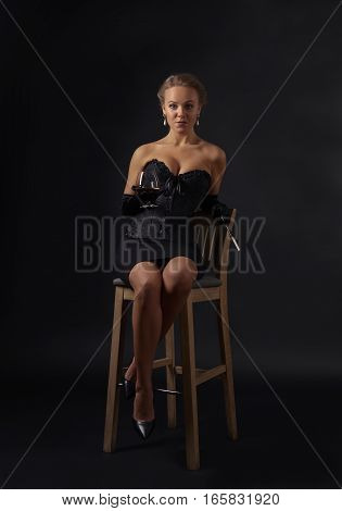Young Beautiful Woman In Black Corset With Glass Of Brandy
