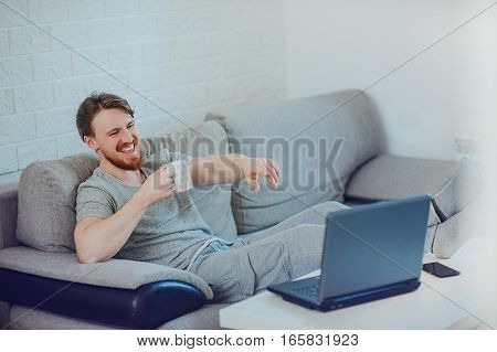 stylish man with a cup of tea working on the computer