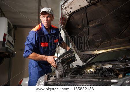 Portait Of Mechanic Fixing Car Engine In Repair Shop