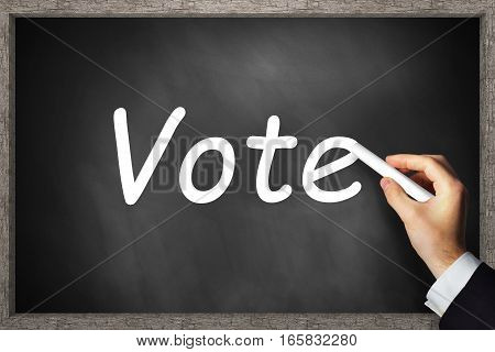 businessmans hand writing vote on black chalkboard