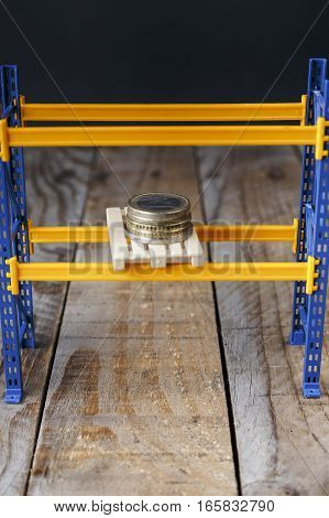 Monkey euro coins on a pallet on a miniature shelf on an old wood