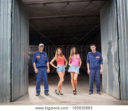 Two auto mechanic man in uniform and two beautiful sexy girls in high heels standing at the entrance to car repair shop