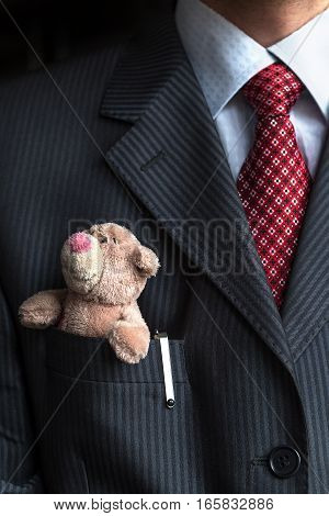 Close up with elegant stylish businessman keeping small teddy bear in his breast suit jacket pocket. Formal negotiations concept