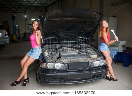 Two Girls Standing By The Car At Auto Repair Shop