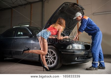 Girl And Man Examining Car Engine At Auto Repair Shop