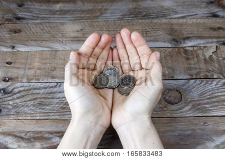 Several euro coins on the hands of a woman