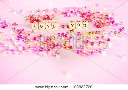Love you text with multicolor beads with pinkish ambient.
