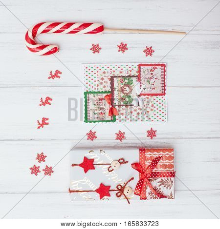 top view of red Christmas gift boxes and Lollipop on a white wood background