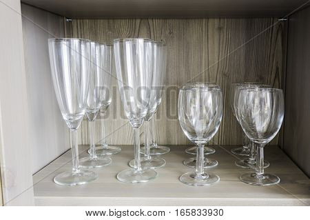 Collection of wine glasses on a wooden shelf