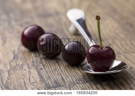 Close-up of cherries in a silver spoon on brown wood background