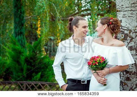 Happy loving wedding couple hugging in the autumn park. Young handsome smiling  groom looking at his beautiful laughing bride in white dress, holding bouquet of red roses, standing near the tree