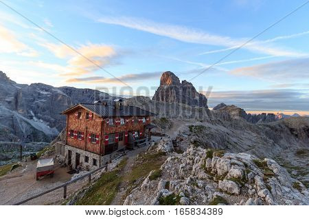 Alpine Hut Bullelejochhutte and mountain Zwolferkofel in Sexten Dolomites at sunrise South Tyrol Italy