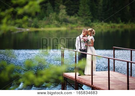 Beautiful young wedding couple, bride and groom posing on lake background. The groom and the bride on pier