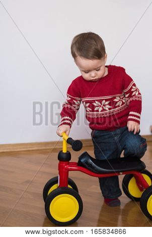 Cute little boy sits on a tricycle. A cute child with cycle at home. Portrait happy funny kid boy on tricycle. Child tricycle.