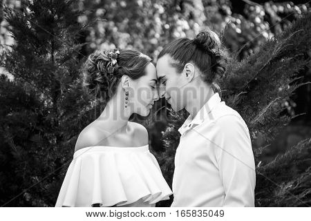 Young wedding couple in love embracing in a park, standing with eyes closed. Portrait of bride and groom. Black and white photo.
