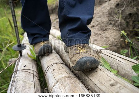 close up of a hikers foot walking on a bamboo makeshift bridge in Colombia