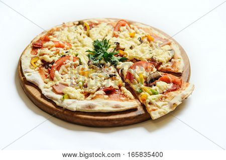 Pizza with ham mushrooms and tomatoes. The meal is on a wooden board on a white background.