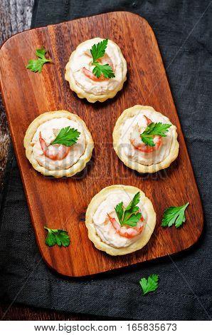 Shrimp salmon mousse parsley tartlets on wood background