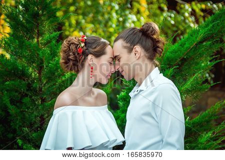 Young wedding couple in love embracing in a park, standing with eyes closed. Portrait of bride and groom.