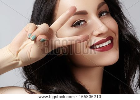 Closeup studio portrait of beautiful sexy young woman with gesturing peace. Perfect retro style ang fashion make-up. happy toothy smile with red lips makeup