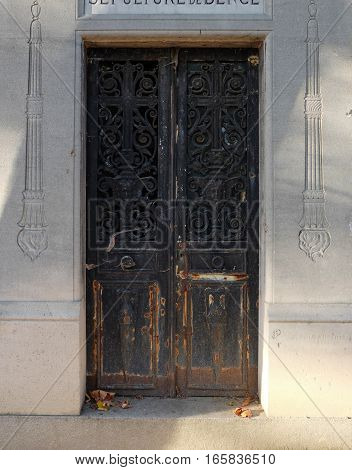 A rusty metal double door of an old tomb at a graveyard with an ornate rectangle arch. Visible ornaments are floral, faces, torches, vases and crosses. The closed door is decaying and rusting, as the crypt is abandoned.