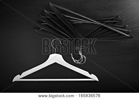 White hanger and a few black hangers, black background, abstract
