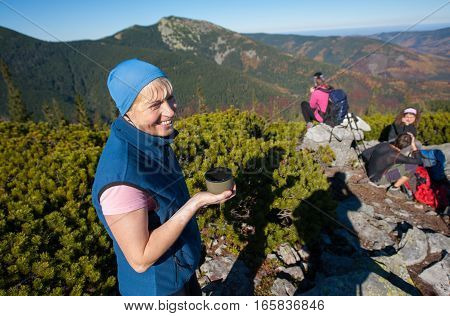 Portrait of old athlete woman drinking tea and smiling on top of the mountain on a warm sunny day fall time. Group of hikers on backgraund. Lifestyle and sport concept.
