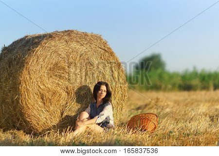 Girl with basket sitting in a field of straw