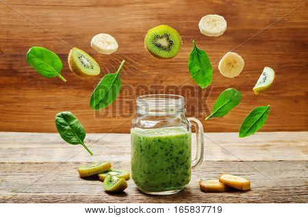 Kiwi banana spinach smoothie with flying pieces.