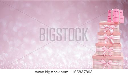 stack of pink gift boxes with satin ribbons on bokeh background. Valentines day