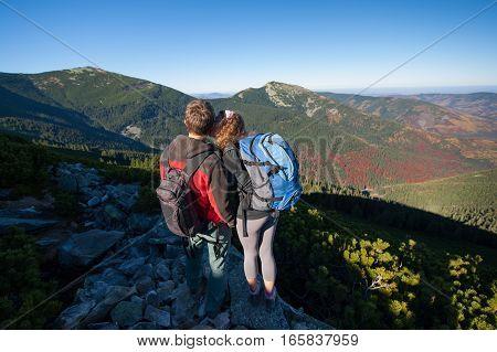 Young Backpackers Couple Enjoying Beautiful Landscape